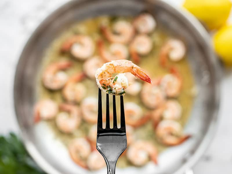 Close up of one garlic butter shrimp with the skillet full in the background