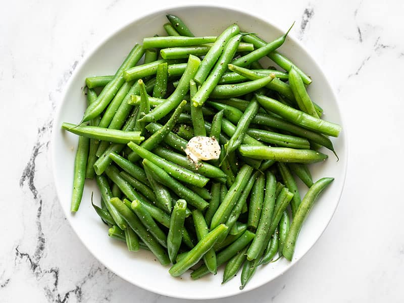 Overhead of a bowl of steamed green beans with butter, salt, and pepper.