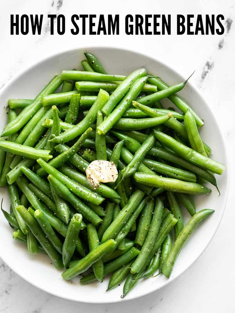 Overhead view of a bowl full of steamed green beans with butter, salt, and pepper