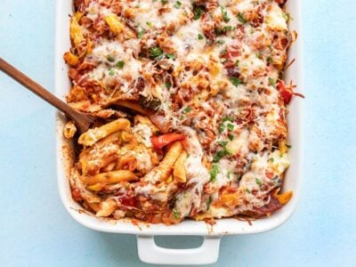 Overhead view of roasted vegetable baked penne being scooped out of the casserole dish