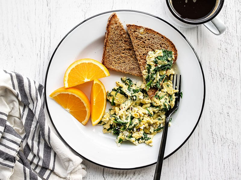 Scrambled eggs with spinach and feta on a plate with toast, half piled onto a slice of toast
