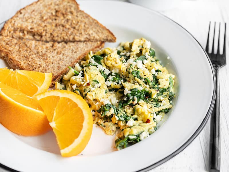 Side view of a plate with scrambled eggs with spinach and feta, toast, and oranges