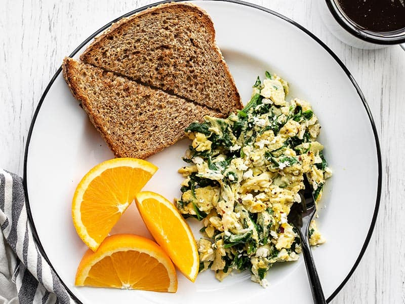 A plate full of scrambled eggs with spinach and feta, toast, and orange slices
