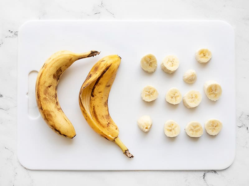 Sliced bananas on a cutting board next to banana peels