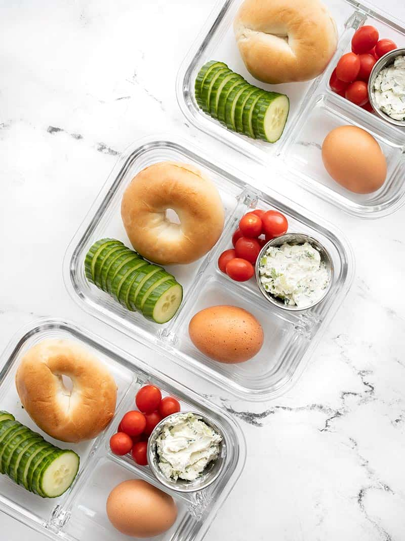 Three glass meal prep containers in a diagonal line filled with the bagel lunch box items