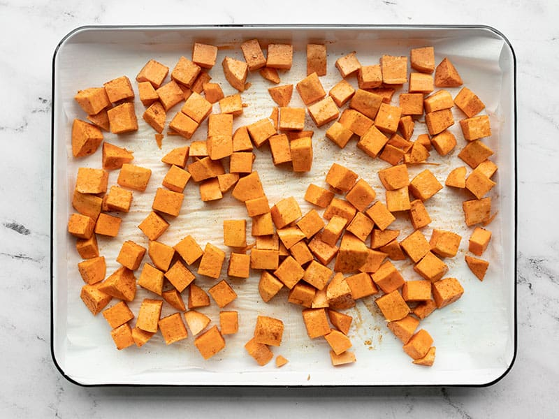 Sweet potatoes prepped for roasting on a sheet pan