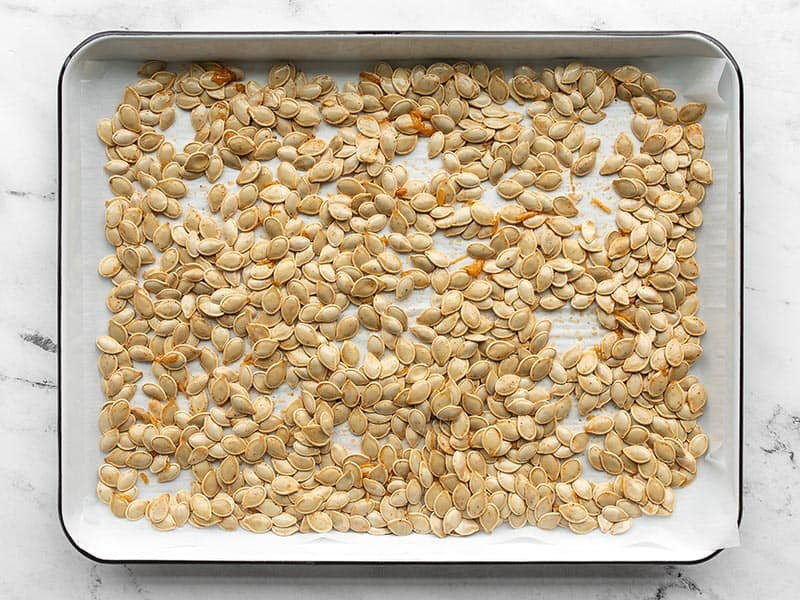 Raw pumpkin seeds on a baking sheet