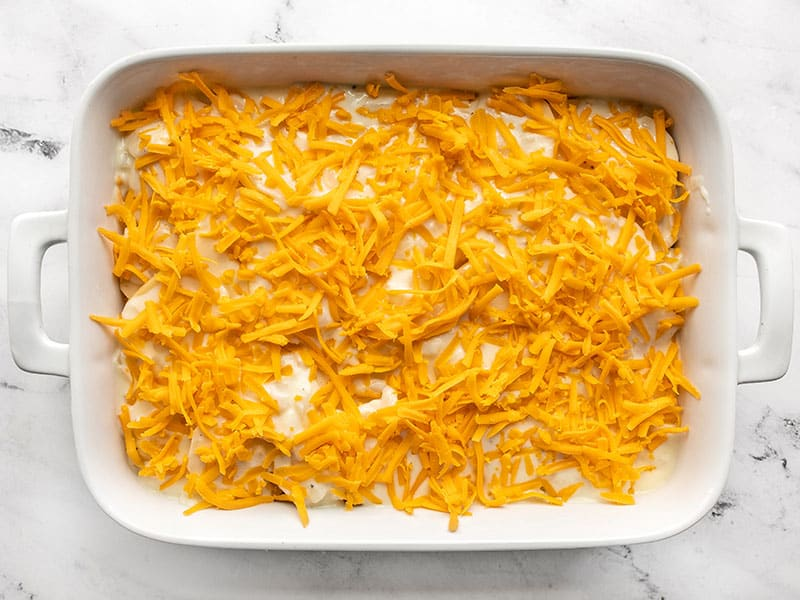 shredded cheese on potatoes in casserole dish