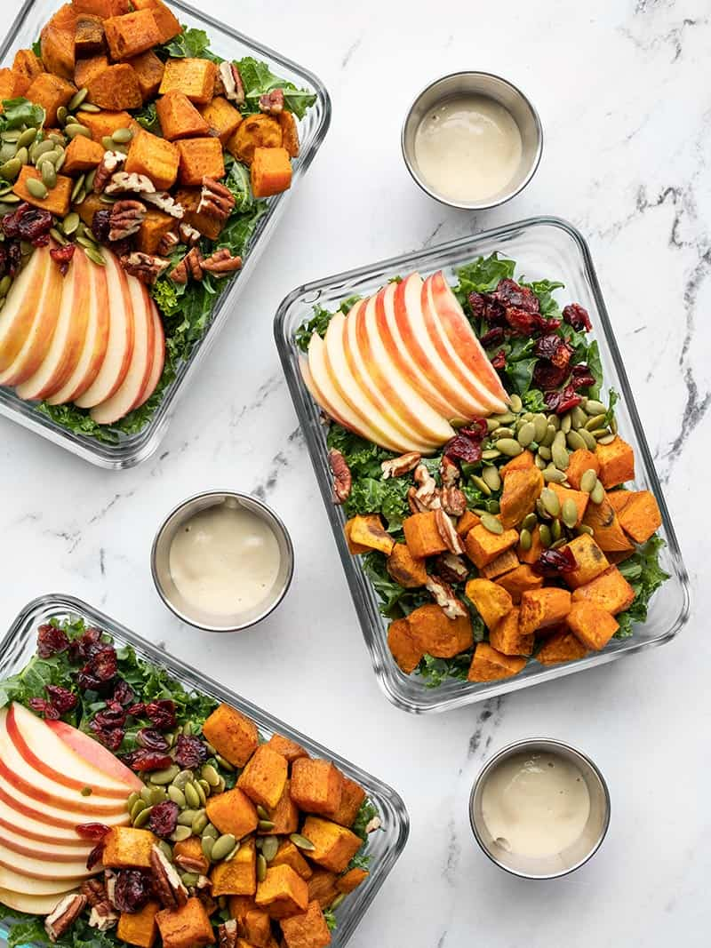Autumn kale and sweet potato salads in glass meal prep containers