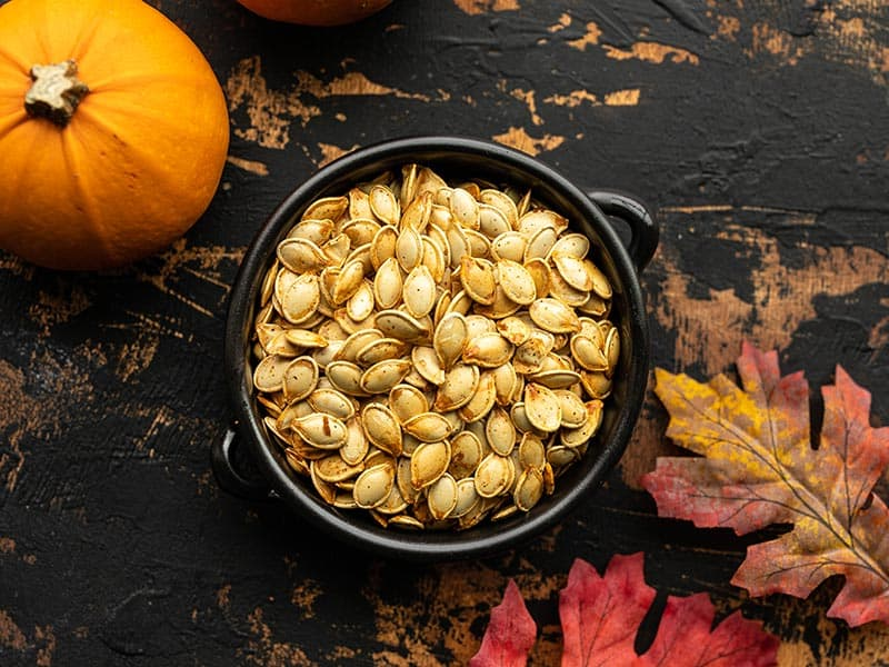 Roasted pumpkin seeds in a small black ceramic bowl with pumpkins and leaves on the sides