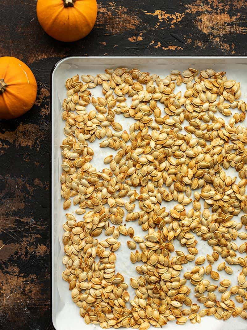 roasted pumpkin seeds on a baking sheet with pumpkins on the side