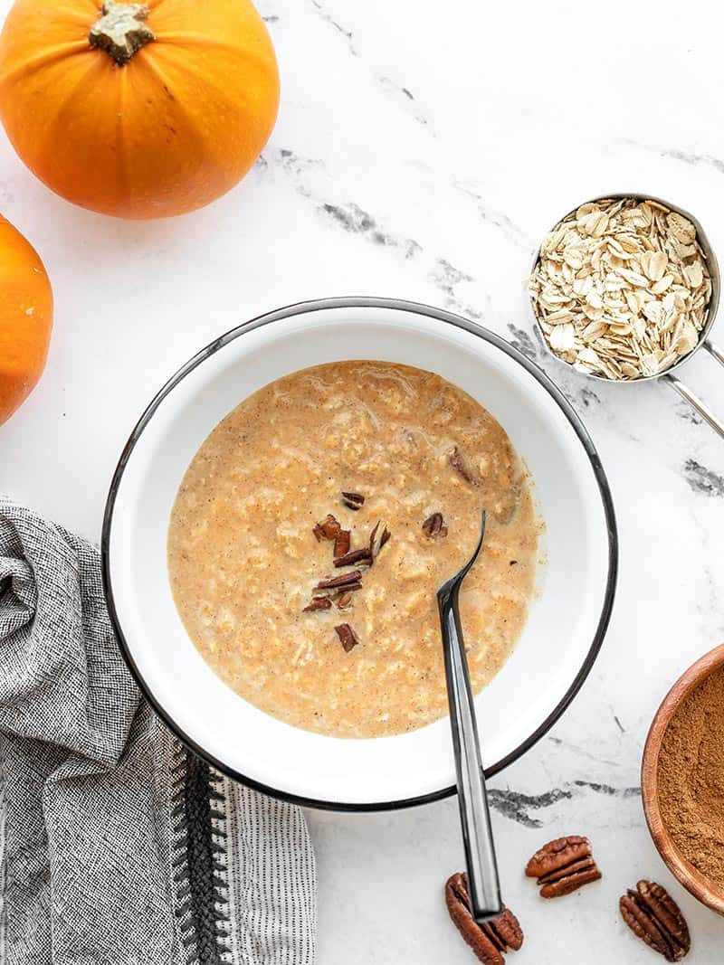 Overhead view of a bowl of overnight pumpkin pie oats with pumpkins, oats, and pecans on the side