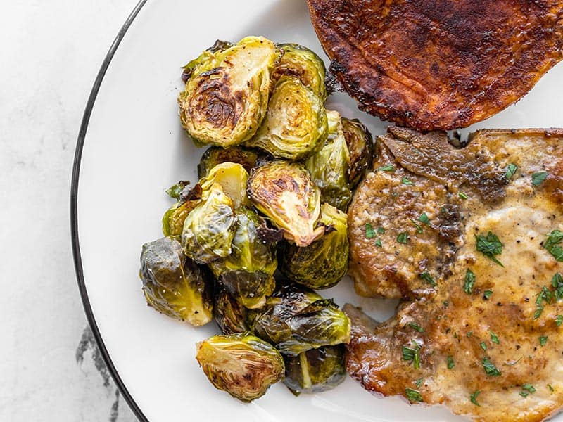 Roasted Brussels sprouts on a plate with pork chops and sweet potatoes