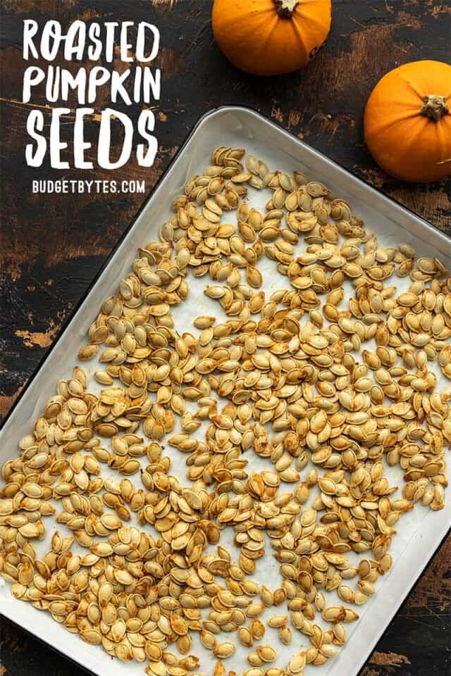 Roasted pumpkin seeds on a baking sheet with title text in the corner