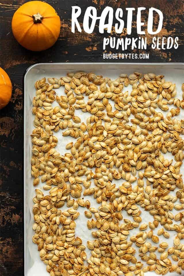 Roasted pumpkin seeds on a baking sheet with title text at the top