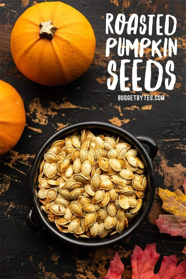 Roasted pumpkin seeds in a black ceramic bowl with title text at the top