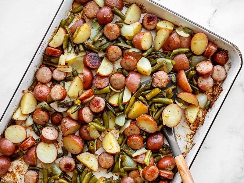Sheet pan roasted kielbasa potatoes and green beans with a spatula