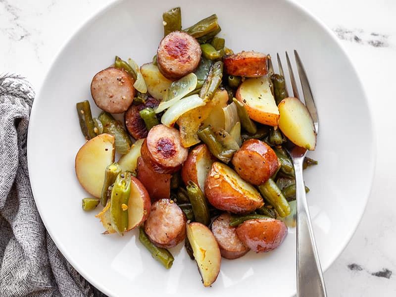 Sheet pan kielbasa, potatoes, and green beans in a bowl with a fork