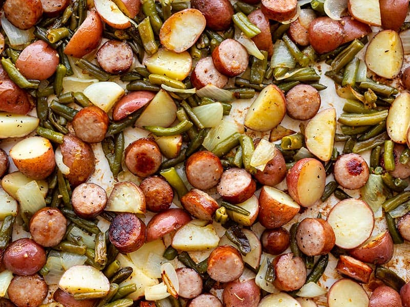 Close up of sheet pan kielbasa potatoes and green beans on a sheet pan