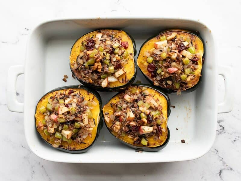 Stuffed and baked acorn squash in a casserole dish