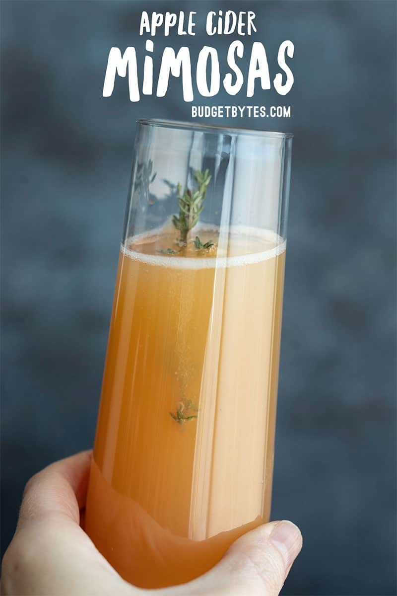 one apple cider mimosa held close to the camera with title text at the top