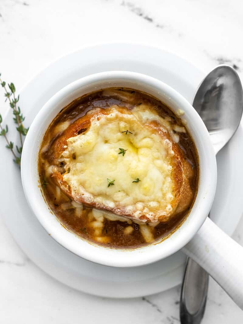 One bowl of french onion soup garnished with fresh thyme, spoon on the side