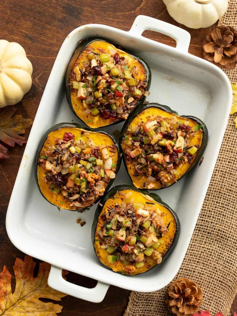 Wild rice stuffed acorn squash in a white casserole dish from above