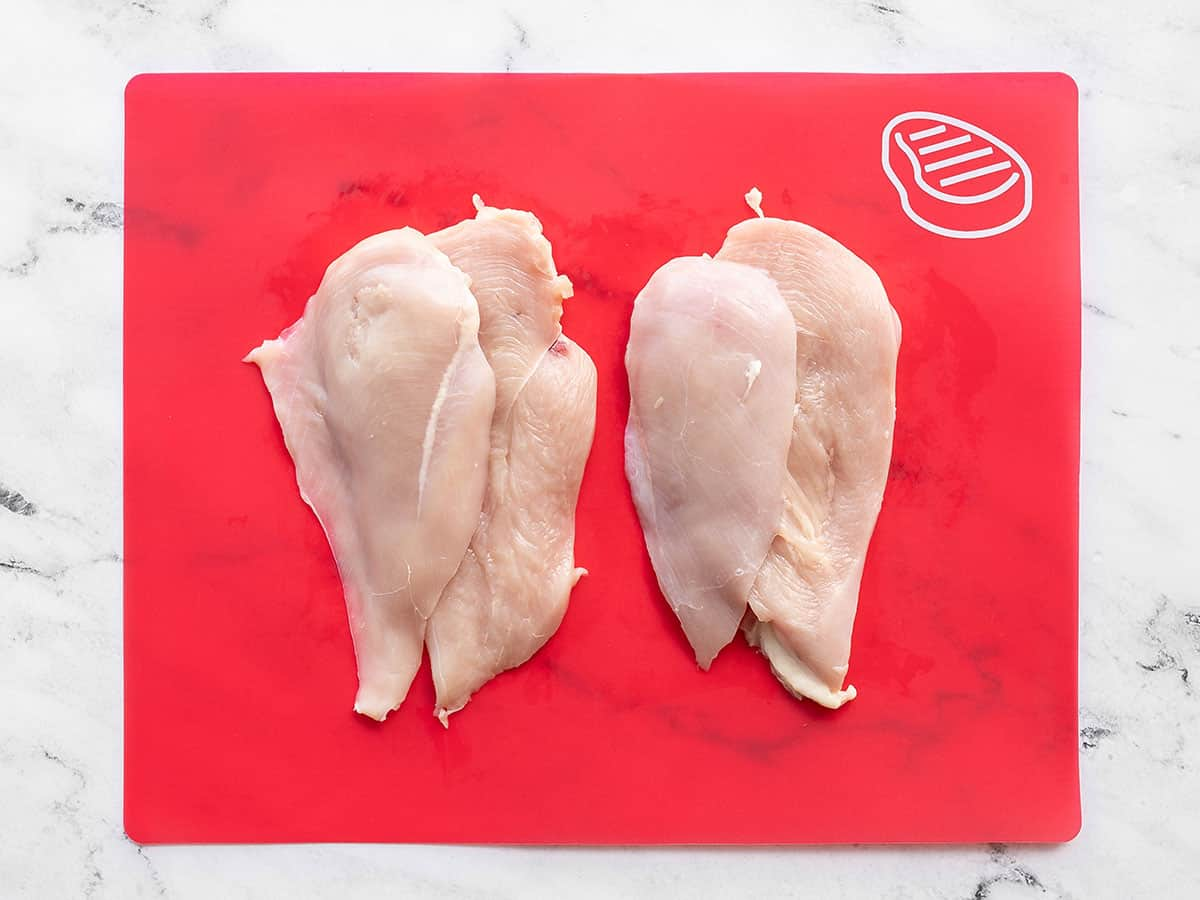 Filleted chicken breasts on a cutting board