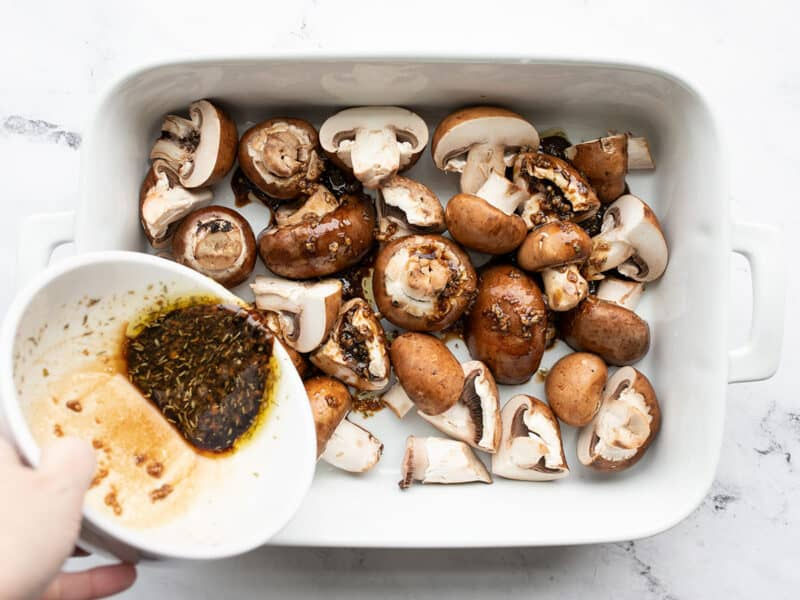 Marinade being poured over the mushrooms in the dish.