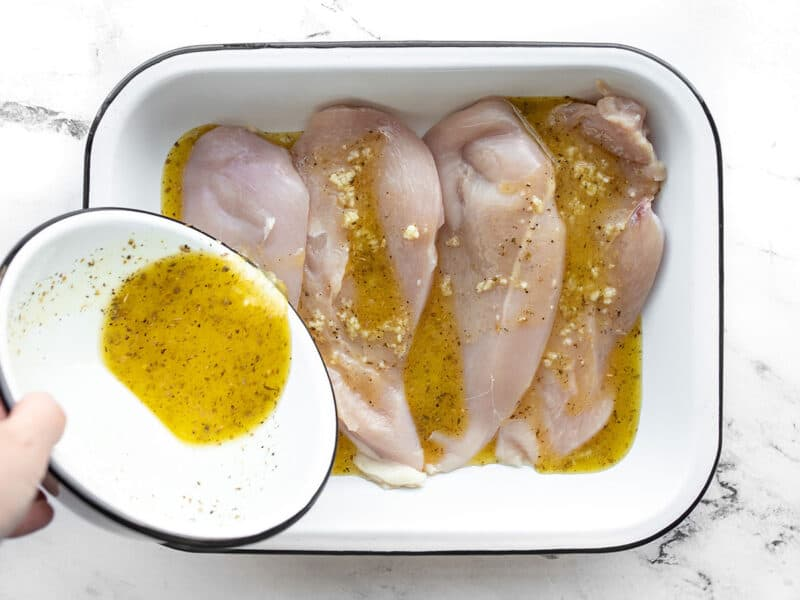 Marinade being poured over the chicken in a dish