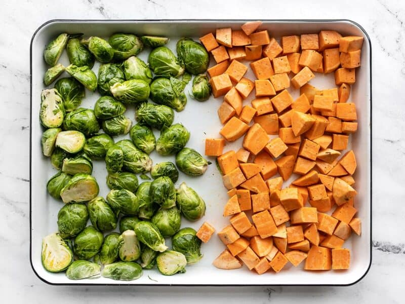 Prepped Brussels sprouts and sweet potatoes on a baking sheet