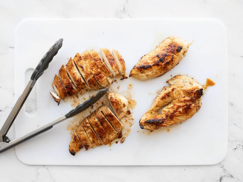 Sliced chicken on a cutting board with tongs