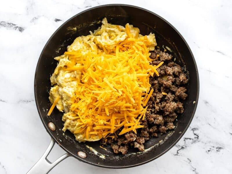 Sausage and cheese added to the skillet with the eggs