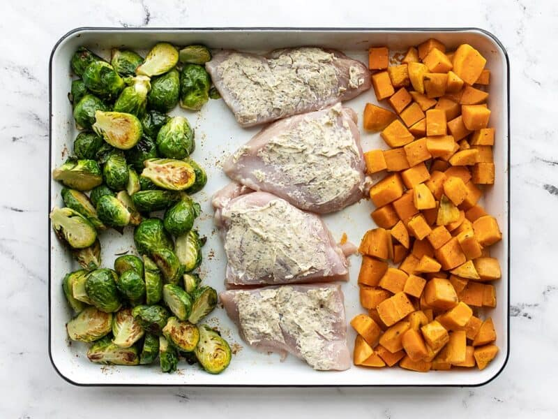 Chicken added to the baking sheet with the roasted vegetables