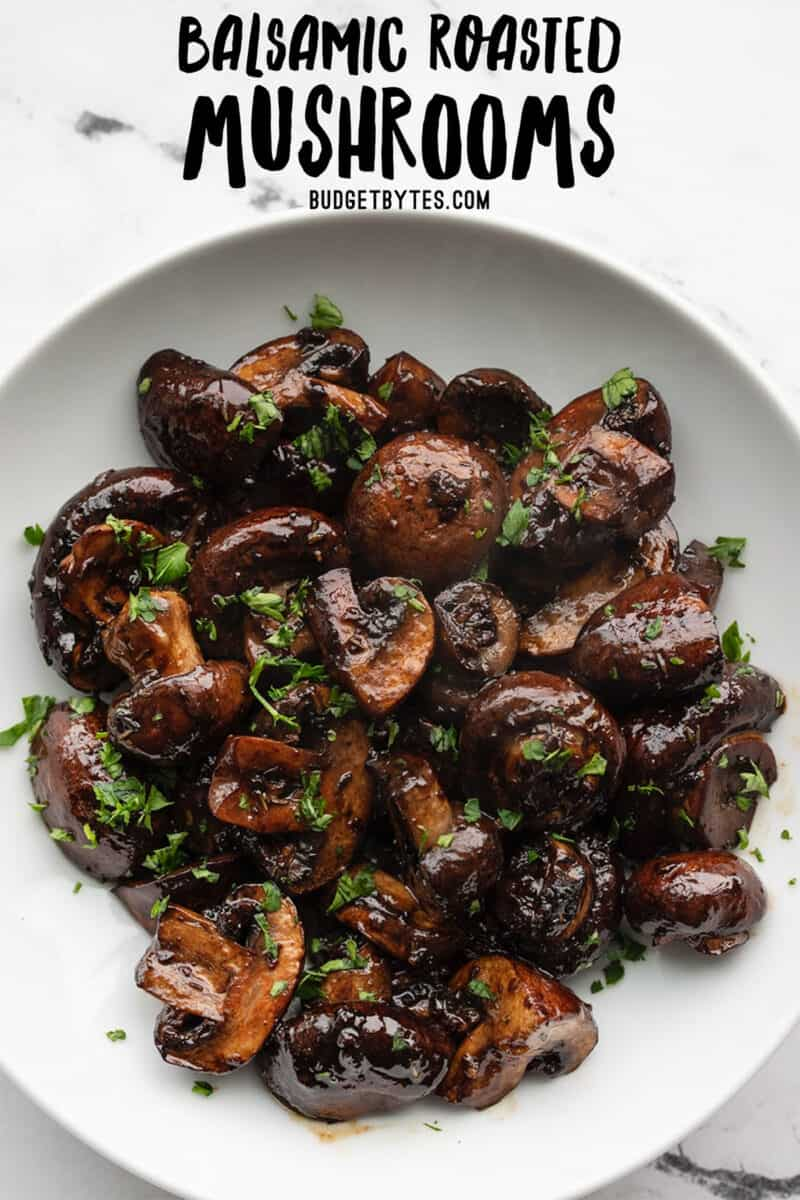 Overhead view of a bowl full of balsamic roasted mushrooms with title text at the top