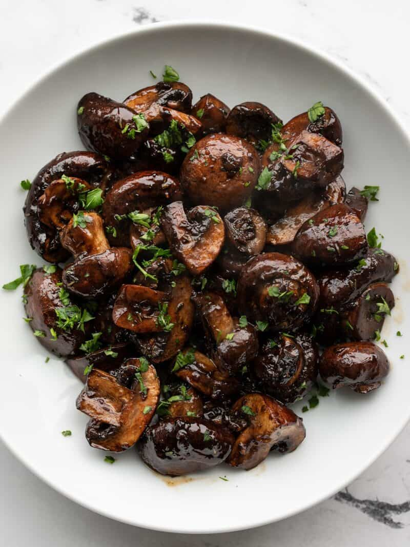 Overhead view of balsamic roasted mushrooms in a white bowl, garnished with parsley