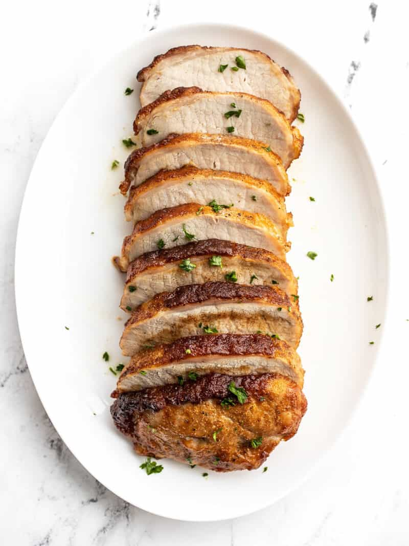 Brown sugar roasted pork loin sliced and served on an oval dish