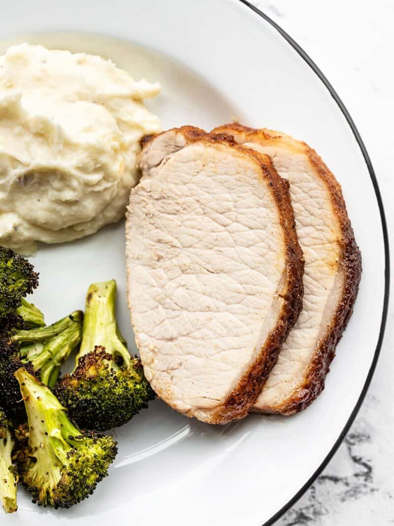 Two slices of roasted pork loin on a plate with broccoli and mashed potatoes