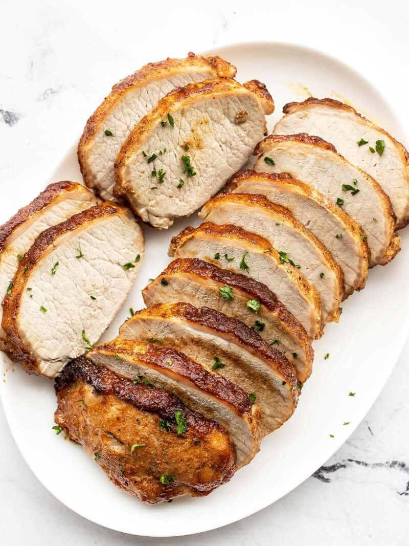 Slices of brown sugar roasted pork loin on a white oval serving dish