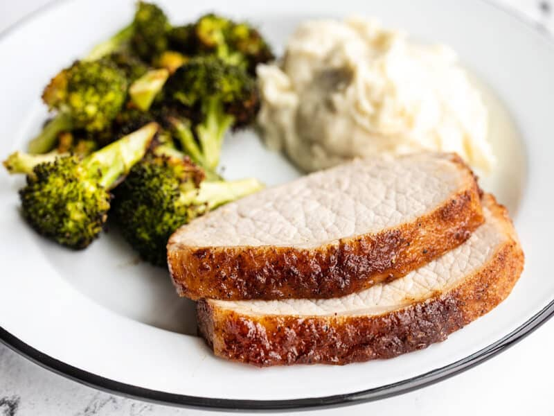 Two slices of pork loin on a plate with broccoli and mashed potatoes, viewed from the side