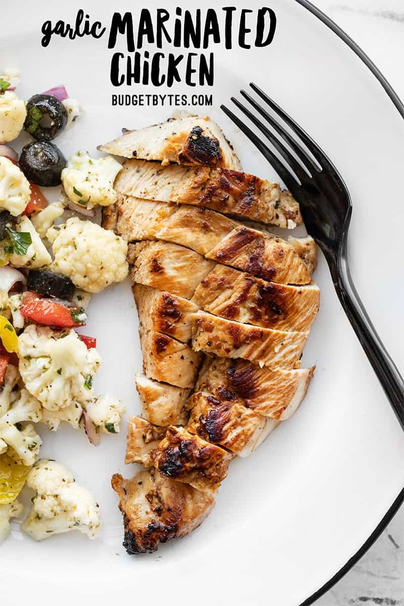 Garlic marinated chicken on a plate with a fork, title text at the top.