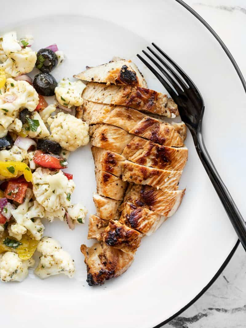 Sliced garlic marinated chicken on a plate with a fork and cauliflower salad