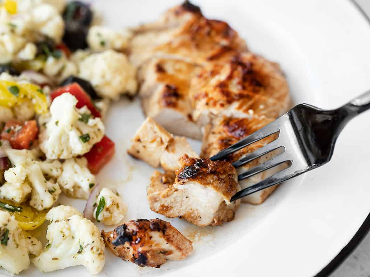 A fork picking up a slice of garlic marinated chicken from a plate