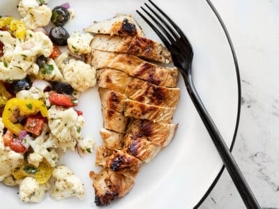 Sliced garlic marinated chicken on a plate with a fork