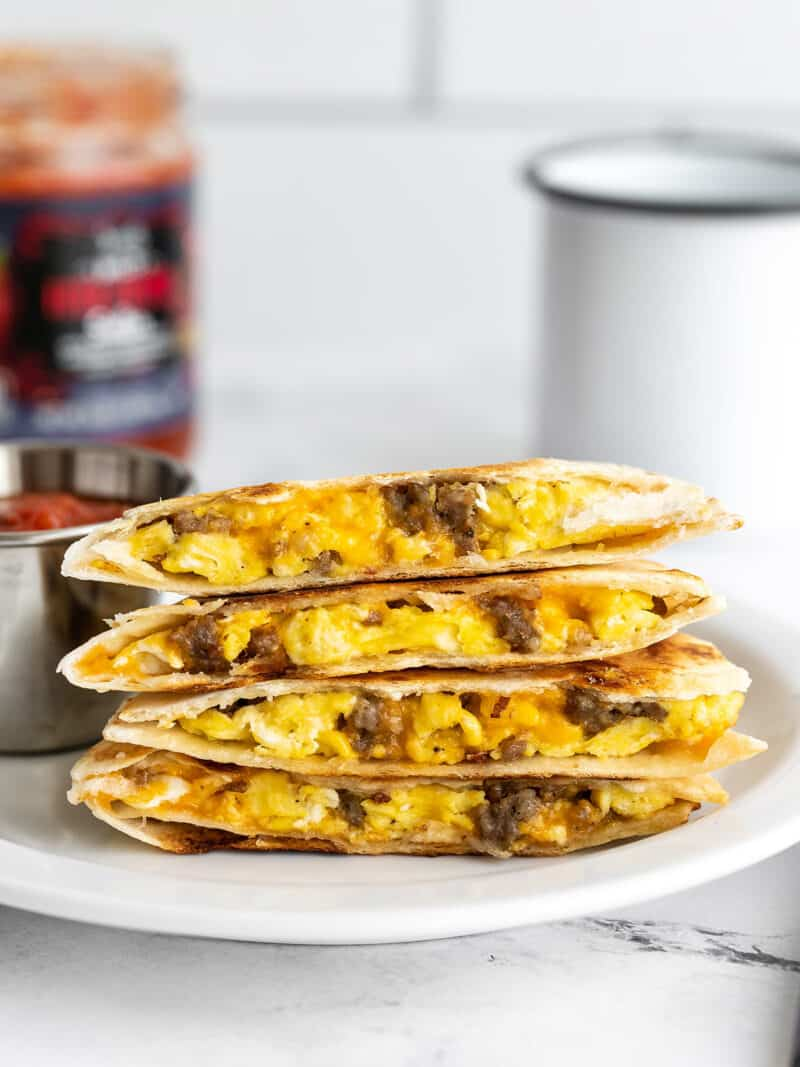 A stack of breakfast quesadillas on a plate with salsa in the background