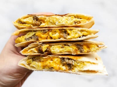 Stacked sausage and egg breakfast quesadillas held close to the camera