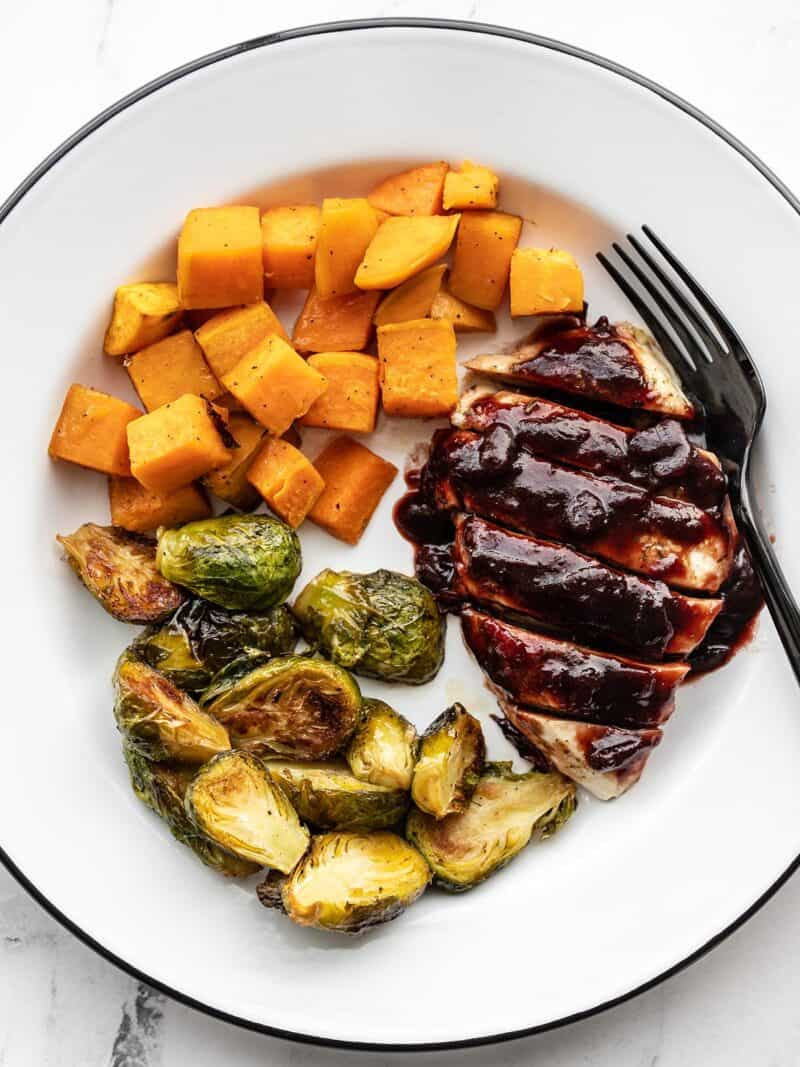 Cranberry chicken on a plate with roasted Brussels sprouts and sweet potatoes