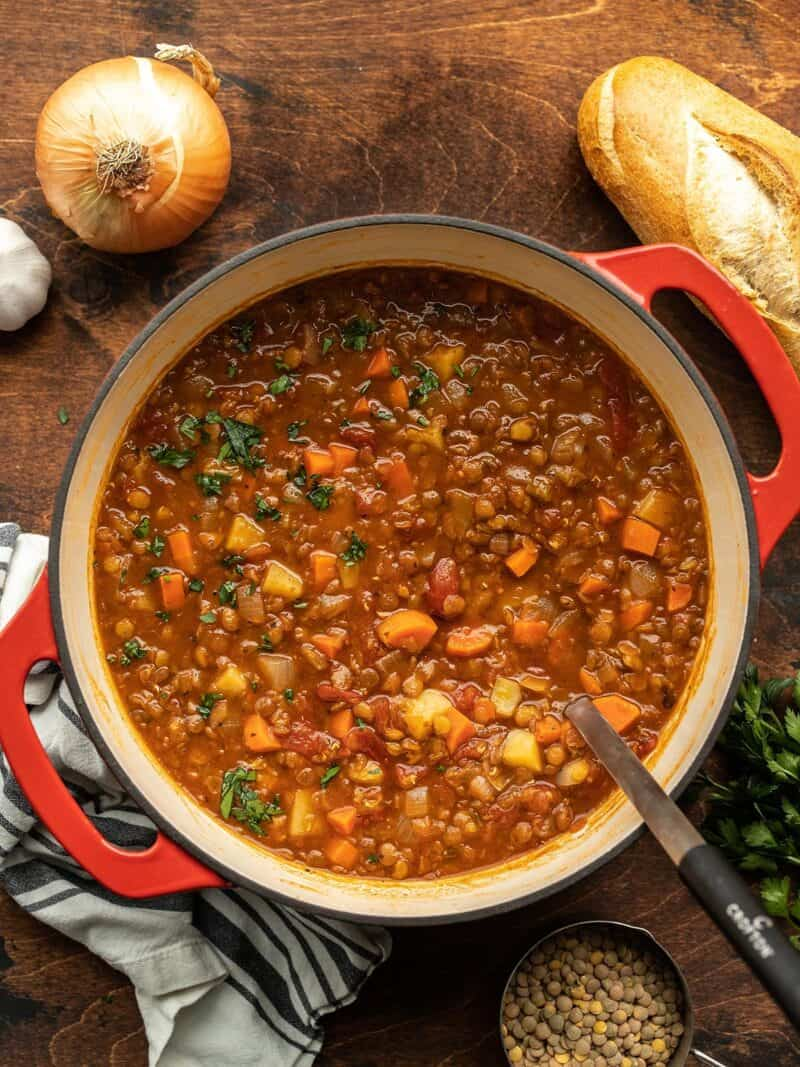 Tomato lentil soup in the pot with bread and vegetables on the sides
