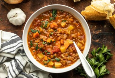A bowl of tomato lentil sup with bread on the side