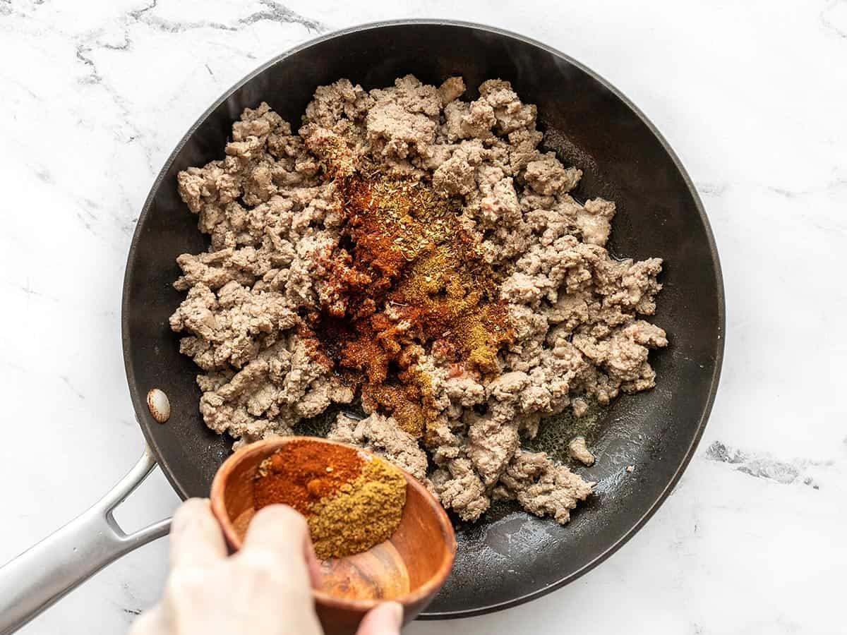 ground turkey cooking in a skillet with taco seasoning being sprinkled over top